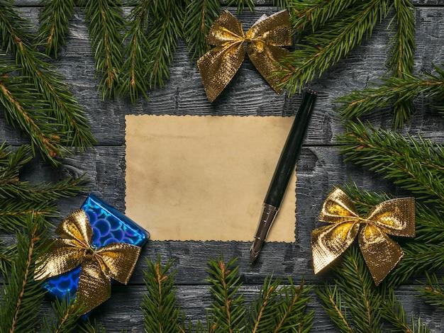 Stylo noeud cadeau et une feuille de papier ancien sur fond de branches de sapin
