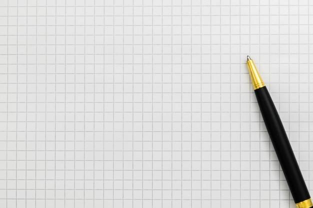 Stylo noir sur close-up de cahier ouvert, espace copie.