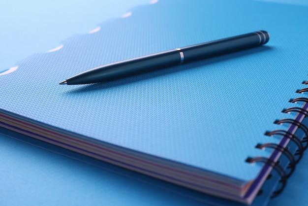 Le stylo noir se trouve sur un cahier bleu avec des documents