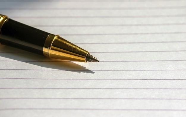Un stylo d'or sur du papier blanc, focus sélectionné