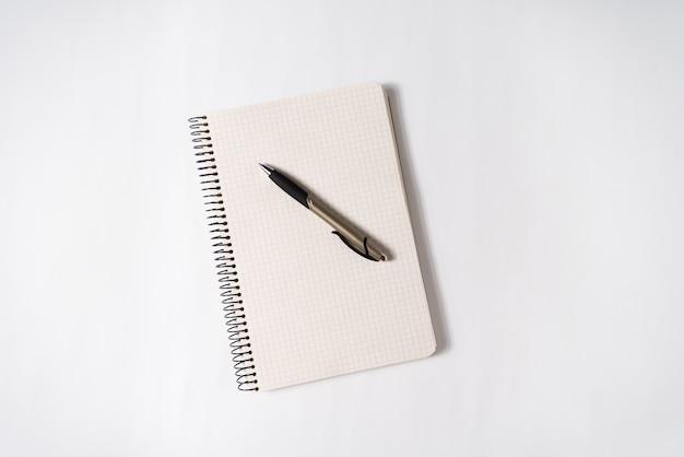 Stylo sur une page vierge d'un cahier ouvert sur blanc