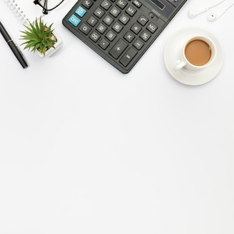 Stylo, plante de cactus, calculatrice, écouteurs et tasse à café sur fond blanc