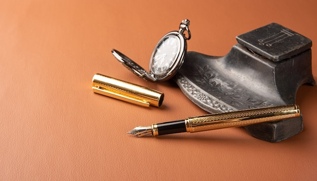 Stylo plume, beaux détails d'un beau stylo plume, un porte-encre ancien et une belle montre gousset posée sur cuir caramel, mise au point sélective.
