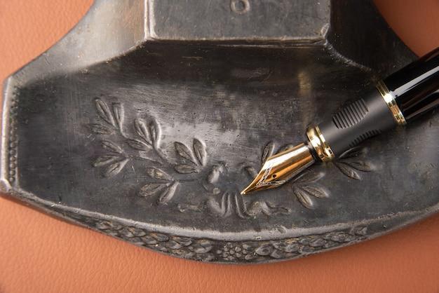 Stylo-plume, beaux détails d'un beau stylo-plume, un porte-encre antique placé sur du cuir caramel, vue de dessus.