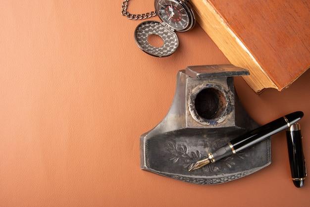 Stylo-plume, beaux détails d'un beau stylo-plume, un porte-encre, une horloge ancienne et un livre ancien posés sur du cuir caramel, vue de dessus.