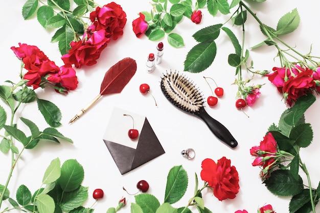 Stylo plume, brosse à cheveux, rouge à lèvres, bague, cerises mûres, petites enveloppes, roses à feuilles vertes reposent sur fond blanc. mise à plat, vue de dessus. cadre fleur. boudoir féminin. lieu de travail