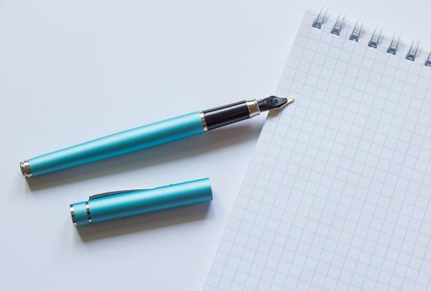 Stylo-plume et cahier sur fond blanc