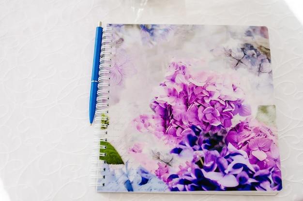 Stylo plume sur cahier, portefeuille avec bouquet de fleurs violettes. espace de copie.