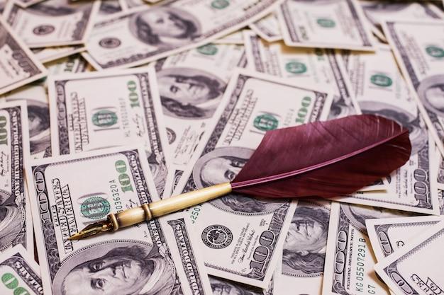 Stylo plume couché sur le fond des billets de cent dollars, fond de l'argent, face avant des billets de cent dollars. fond de dollars, vieux visage de billet de cent dollars