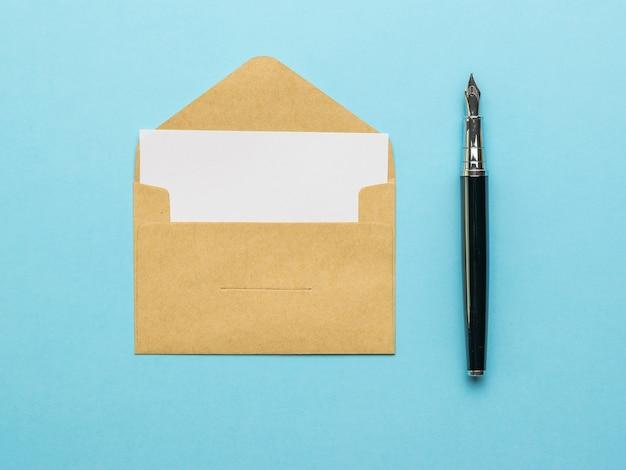 Un stylo plume et une enveloppe postale ouverte avec une feuille blanche sur fond bleu. mise à plat.