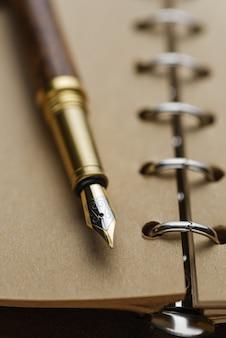 Stylo plume marron sur un cahier avec des pages jaunes.