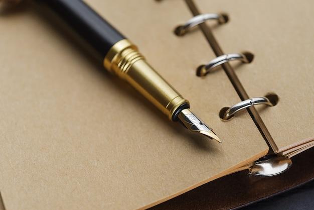 Stylo plume noir sur un cahier avec des pages jaunes.