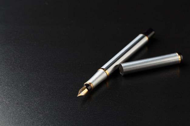 Stylo-plume avec un tracé de détourage sur fond noir