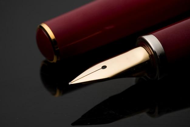 Stylo-plume avec un tracé de détourage sur fond noir.