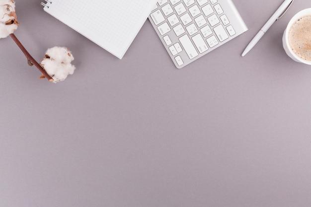Stylo près d'un cahier, d'un clavier, d'une brindille et d'une tasse