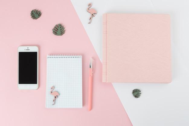 Stylo près de cahier, smartphone, album et petites décorations