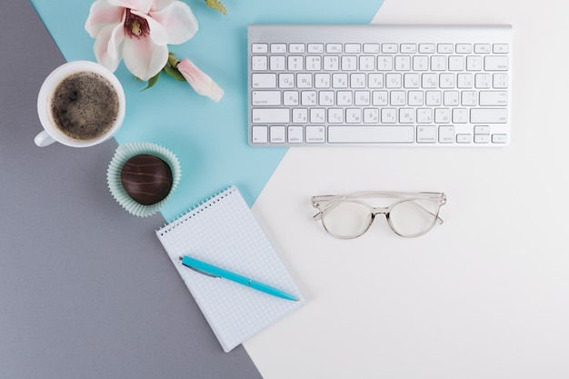 Stylo près de cahier, tasse, biscuit, fleur, lunettes et clavier