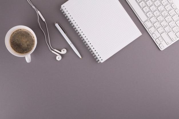 Stylo près du bloc-notes, d'une tasse, d'écouteurs et d'un clavier