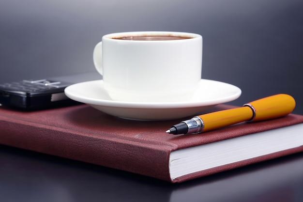 Le stylo rouge est une soucoupe tasse de café noir. sujets pour le travail dans le bureau et l'éducation