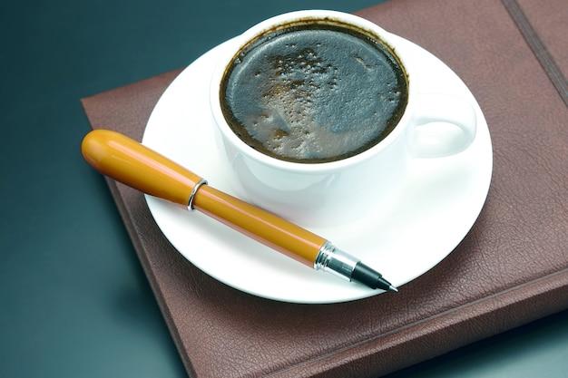 Stylo rouge sur une tasse blanche de café noir. boisson chaude