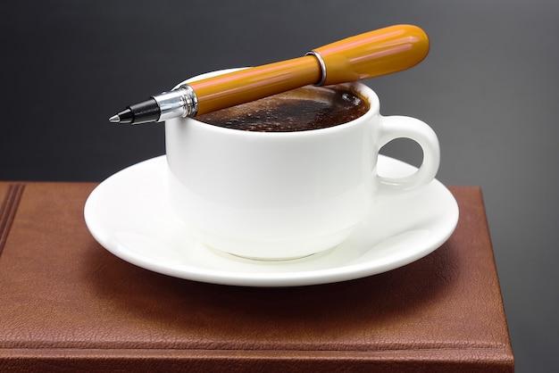 Stylo rouge sur une tasse blanche de café noir. sujets pour le travail dans le bureau et l'éducation