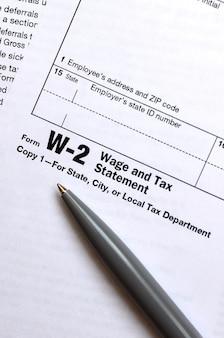 Le stylo se trouve sur le formulaire d'impôt w-2 déclaration de salaire et d'impôt. le temps de payer des impôts