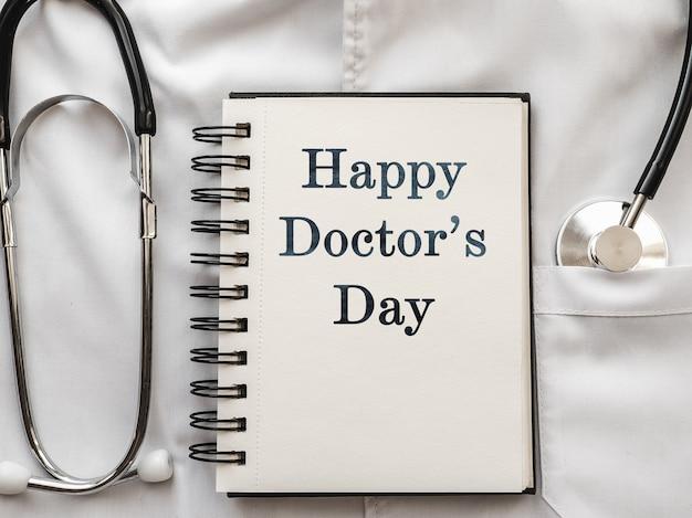 Stylo, stéthoscope, masque facial et lunettes allongés sur une blouse médicale. bonne fête des médecins. gros plan, pas de monde. félicitations aux parents, amis et collègues