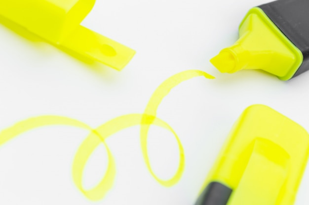 Stylo surligneur jaune et griffonnages isolé on white