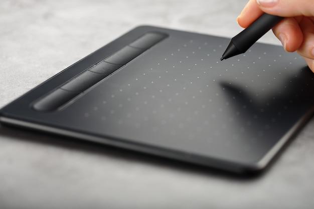 Stylo avec une tablette graphique dans les mains du concepteur, gros plan. gadget pour l'art et le travail.