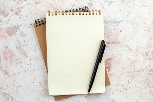 Stylo vue de dessus sur des cahiers à spirale sur fond aquarelle nue