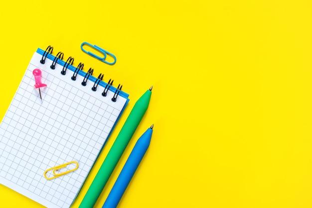 Stylos bleus et verts et bloc-notes ouvert avec une feuille vierge sur une surface jaune