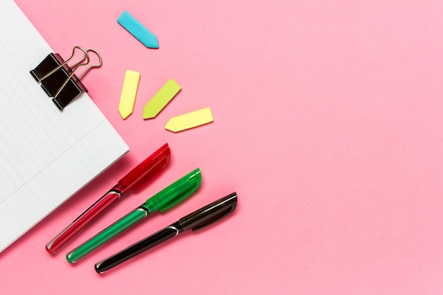 Stylos de couleur, notes autocollantes, cahier rose