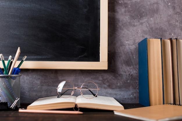 Stylos, crayons, livres et verres sur la table, dans le contexte du tableau