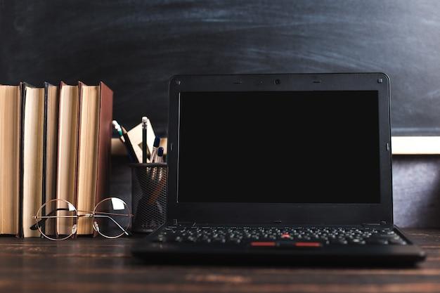Stylos, pomme, crayons, livres, ordinateur portable et lunettes sur la table, sur fond de tableau