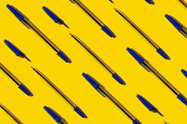 Stylos à répétition bleus sur fond jaune