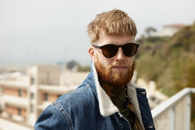 Stylsih mal rasé jeune homme de race blanche en lunettes de soleil rectangulaires noires et veste en jean relaxant
