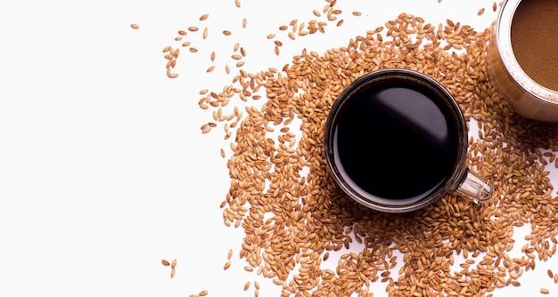 Substitut de café décaféiné d'avoine dans une tasse sur un fond blanc à côté des ingrédients. copiez l'espace. vue d'en-haut