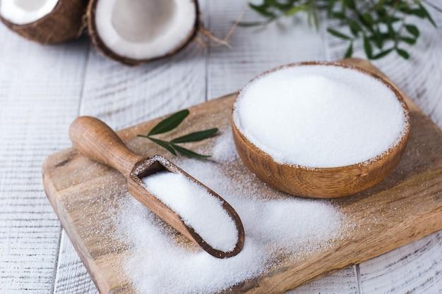 Substitut de sucre dans un bol en bois sur fond de noix de coco. édulcorant naturel. stevia, érythritol.