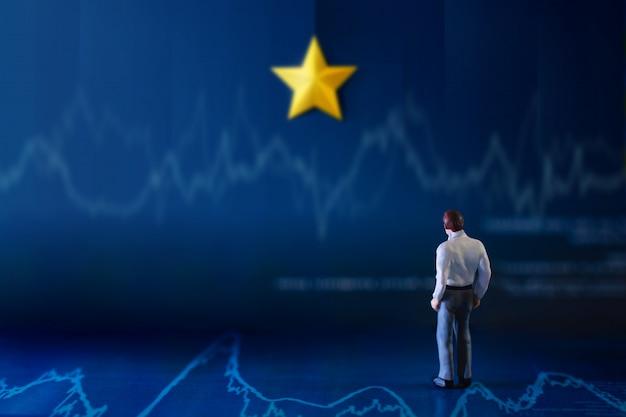 Succès en affaires ou concept de talent. un homme d'affaires miniature se tenant sur le graphique financier et regardant sur le mur avec l'étoile dorée jaune