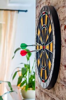 Succès atteignant cible objectif objectif réalisation concept background - fléchettes dans l'oeil de boeuf se bouchent. flèches rouges et vertes dans le concept d'objectif commercial du centre cible