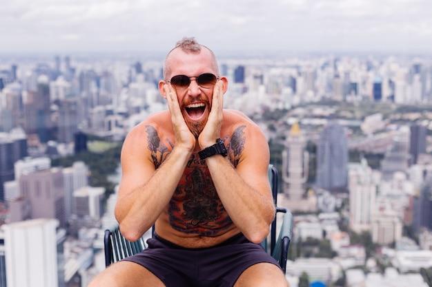 Succès bel homme fort tatoué brutal barbu européen aux seins nus avec montre est assis sur une chaise à l'étage élevé avec vue imprenable sur la ville