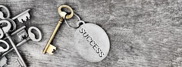 Succès gravé sur un anneau d'une clé ancienne en or sur une surface en bois avec d'autres clés en argent