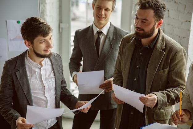 Succès. groupe de jeunes professionnels ayant une réunion. un groupe diversifié de collègues discute de nouvelles décisions, plans, résultats, stratégie. créativité, lieu de travail, affaires, finance, travail d'équipe.