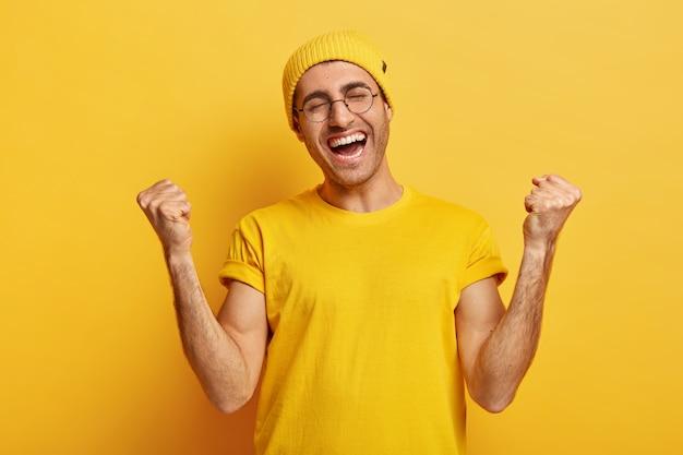 Succès heureux jeune homme serre les poings en geste de victoire, reçoit la place de champion