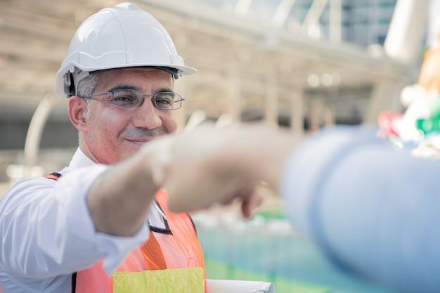 Succès d'ingénieurs seniors se cognant les poings avec des collègues