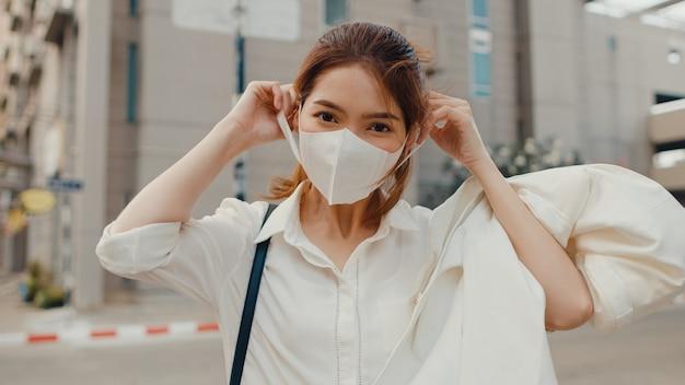 Succès jeune femme d'affaires asiatique en vêtements de bureau de mode portant un masque médical souriant dans la rue