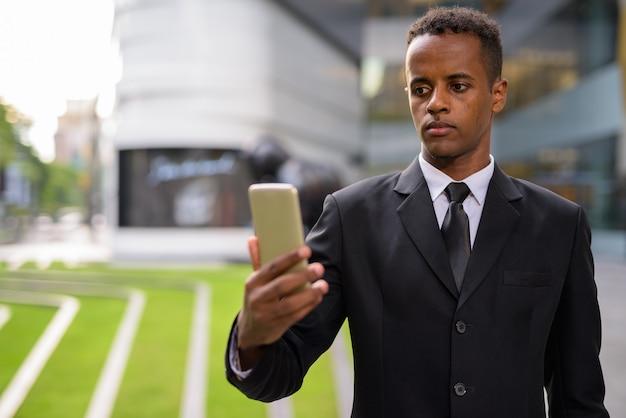 Succès jeune homme d'affaires africain utilisant un téléphone mobile à l'extérieur