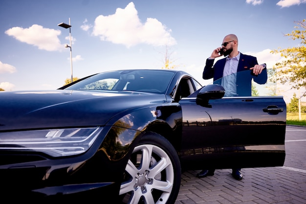 Succès jeune homme avec un téléphone près d'une voiture dans un parking.