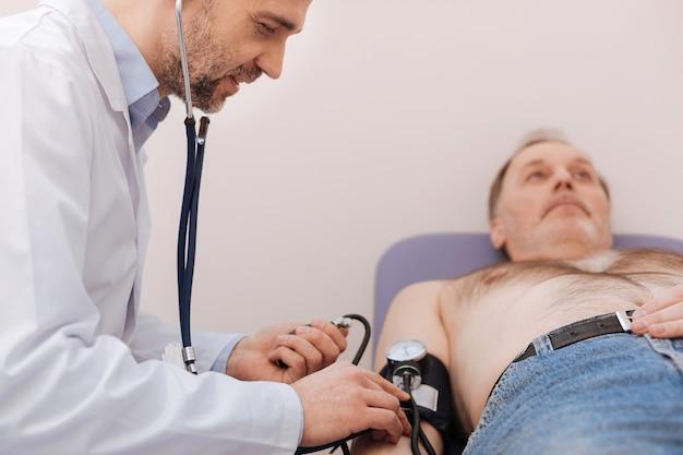 Succès d'un merveilleux médecin privé effectuant un bilan de santé général de son patient et mesurant sa pression alors qu'il était allongé sur un lit