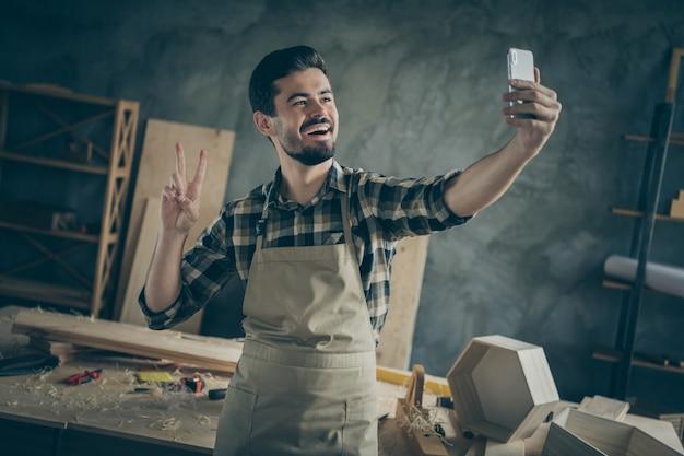 Succès positif entrepreneur de restauration de meubles en bois dur workman make selfie sur smartphone show v-sign profiter de son lieu de travail dans le garage